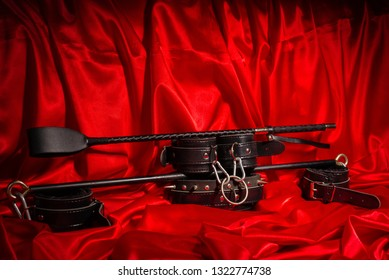 Close up bdsm outfit. Bondage, kinky adult sex games, kink and BDSM lifestyle concept with a pair of leather handcuffs, flogger, whip on red silk with copy space.