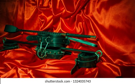 Close up bdsm outfit. Bondage, kinky adult sex games, kink  lifestyle concept with a pair of leather handcuffs, flogger, whip on red silk with copy space.