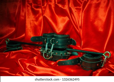 Close up bdsm outfit. Bondage, kinky adult sex games, kinky lifestyle concept with a pair of leather handcuffs, flogger, a leash attached on red silk with copy space.