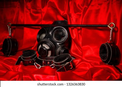 Close up bdsm outfit. Bondage, kinky adult sex games, kinky lifestyle concept with a pair of leather handcuffs, flogger, gas mask on red silk with copy space.