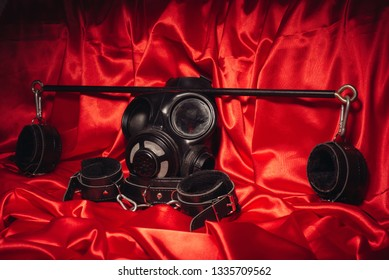 Close up bdsm outfit. Bondage, kinky adult sex games, kink and BDSM lifestyle concept with a pair of leather handcuffs, flogger, gas mask on red silk with copy space.