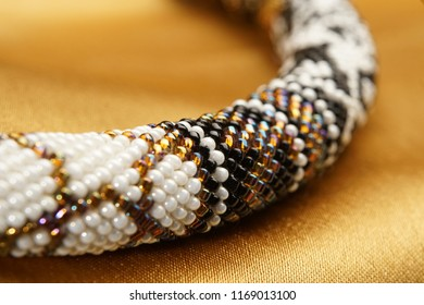 Close up of bead rope, seed beads, bead necklace. White bead necklace on a gold satin
