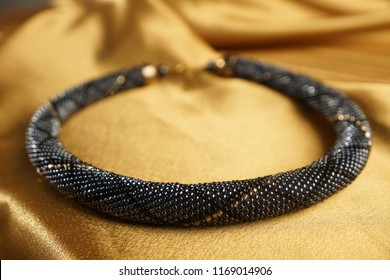 Close up of bead rope, seed beads, bead necklace. Black bead necklace on a gold satin