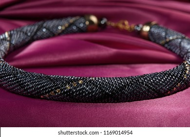 Close up of bead rope, seed beads, bead necklace. Black bead necklace on a red satin