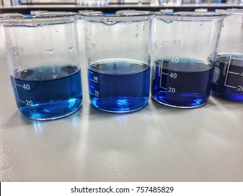 Close up Beakers in chemistry laboratory fill with blue solution clear indicator for detecting phosphate experiment. Can use as a science background or equipment in laboratory photo.