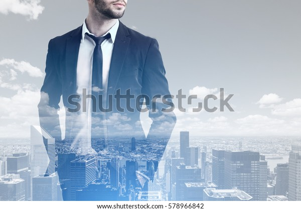 Close up of a bearded businessman standing with his hands in pockets against a morning city panorama. Mock up. Double exposure