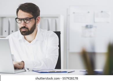 Close up of a bearded businessman wearing glasses and sitting at his laptop and typing. There is a whiteboard and a bookcase in the background.