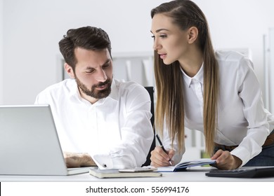 Close up of a bearded businessman and a woman with long hair standing beside him in office. She is taking notes. He is looking at her hands.