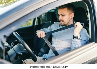 Close up of bearded Caucasian man putting seat belt while sitting in his car.
