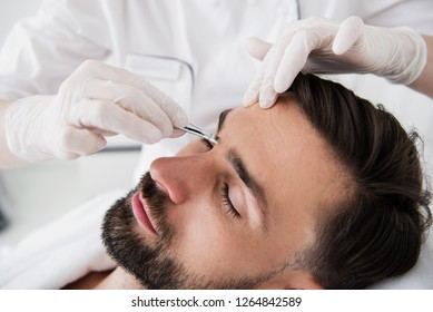 Close up of bearded man closing eyes and hands in rubber gloves holding tweezers and plucking his eyebrows