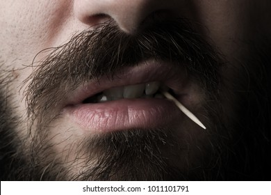 Close Up of a Bearded Man's Mouth with a Wood Toothpick