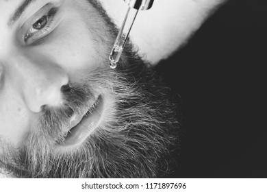 Close up of beautician applying gel serum on bearded man face using glass pipette