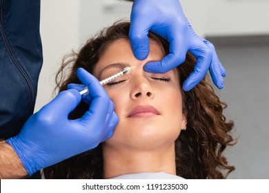 Close up of beautician expert's hands injecting botox in female forehead.