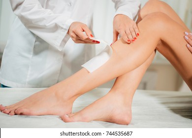 Close Up Beautician Waxing A Womans Leg Applying A Strip Of Material Over The Hot Wax