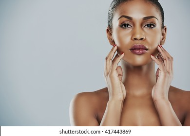 Close up of beautiful African bare shouldered female with both hands on cheeks over gray background with copy space on one side