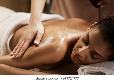 Close up of beautiful african girl enjoying massage in spa salon.