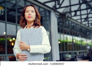 close up beautiful asian businesswoman holding resume folder at outside company building for looking job interview concept