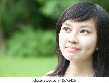 Close up of Beautiful Asian Chinese/Japanese girl daydreaming for ideas outdoors