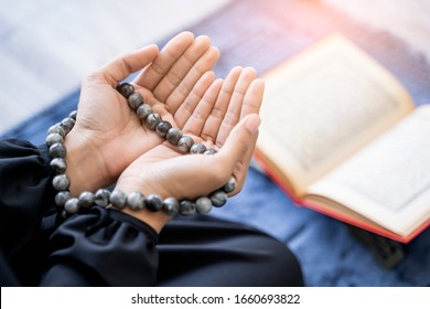 Close up beautiful asian muslim woman putting hands up to chest praying to allah with misbaha praying bead in hands sitting on knees on praying mat with quran resting on stand, bright light sunshine