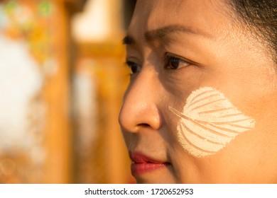 Close up beautiful Asian tourist woman paint tanaka powder on her cheeks and dress Burmese national costume during travel in Mandalay ,Myanmar