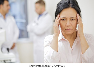 Close up of a beautiful Asian woman having headache rupping her temples standing at the hospital copyspace healthcare medicine illness painful stressful unhappy doctors treatment therapy concept