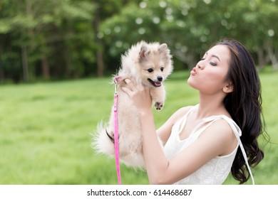 Close up Beautiful Asian woman playing with dog,