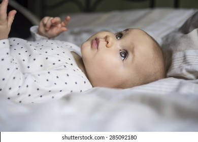 close up of a beautiful baby laying on a bed