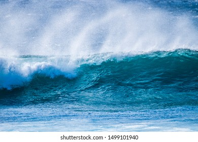 close up of beautiful and bigs blue and green waves breaking - pacific or athlantic ocean - blue sea and great place to surf