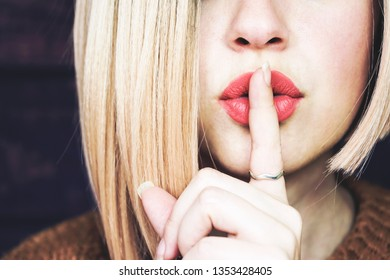 Close up of a beautiful blonde woman doing a silent gesture