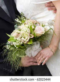 A close up of a beautiful bridal bouquet held by the bride and groom