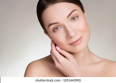 Close up of a beautiful brunette caucasian woman with fresh clean natural skin and soft smile on her face. Neutral, daily make up