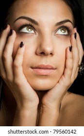 Close up of a beautiful brunette touching her face with hands