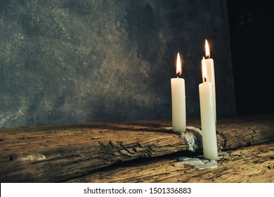 Close up beautiful burned candles on a old oak wooden table and dark gray wall background.