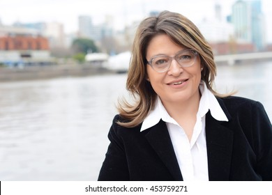 Close up of a beautiful business woman with glasses standing outdoors.