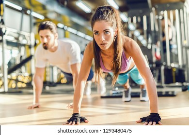 Close up of beautiful Caucasian woman doing push-ups in gym. In background her personal trainer showing exercises.