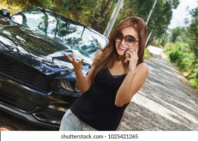 Close up of beautiful caucasian woman using her cellphone and wearing sunglases, black t-shirt and jeans, having a problem with black car on a roadtrip. Upset woman emotionally reacting on overheated