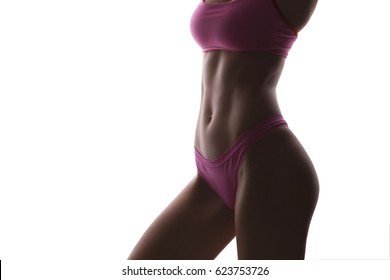 Close up of a beautiful caucasian young woman fit athletic body in sportswear pumping up abdominal muscles. Neutral white isolated background
