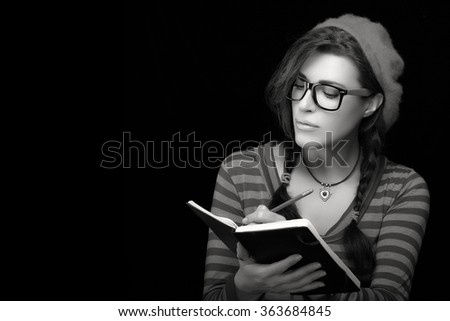 0d7e607142 Close up beautiful college girl in trendy outfit writing on her notebook.  Monochrome portrait isolated