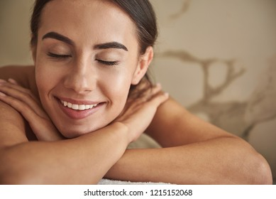 Close up of beautiful dark haired lady closing her eyes and smiling while lying on the white towel in hammam