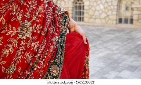 Close up beautiful ethnic Indian Saree. Young woman in red, colorful, sensual, wedding and very feminine outfit - Indian sari walks along old streets in India.
