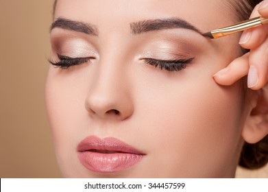 Close up of beautiful face of young woman getting make-up. The artist is applying eyeshadow on her eyebrow with brush. The lady closed eyes with relaxation