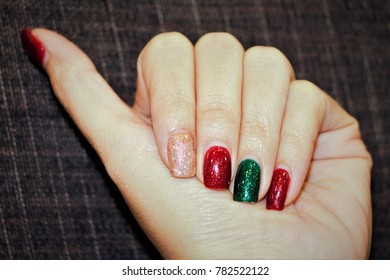 Close up beautiful female hand with glitter nails polished. Red nails. Green nail. Glitter nail.