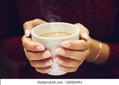 Close up of beautiful female hands holding big white cup of cappuccino coffee. Woman wearing warm winter knitted red sweater. Toned.