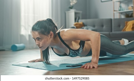 Close Up of a Beautiful Fitness Girl in an Athletic Top Doing Push Up Exercises While Using a Stopwatch on Her Phone. She is Training at Home in Her Living Room with Minimalistic Interior.