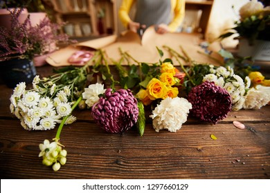 Close up of beautiful flowers lying on wooden table in flower shop, copy space