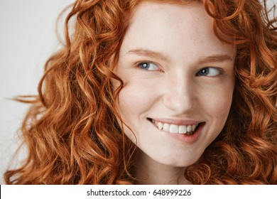 Close up of beautiful girl with curly red hair and freckles smiling biting lip over white background.