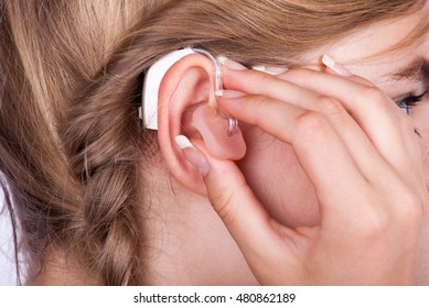 Close up of a beautiful girl's head inserting a hearing aid in her ear