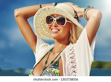 Close up of beautiful happy blonde woman in hat and sunglasses