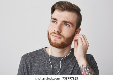 Close up of beautiful joyful charming young caucasian male student with stylish hairstyle, beard and tattoo on arm in casual gray t-shirt looking aside with happy and dreamy expression, holding