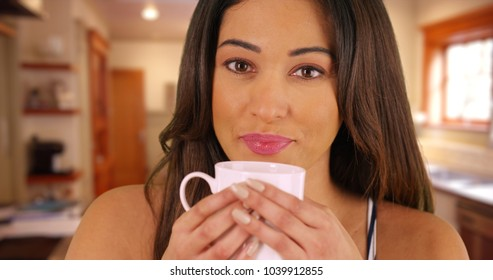 Close up of beautiful Latina female holding a coffee mug inside kitchen
